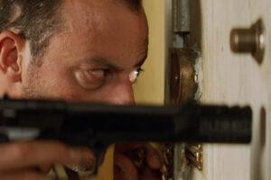 Leon 1994 Movie Jean Reno holding a gun and looking through spyhole