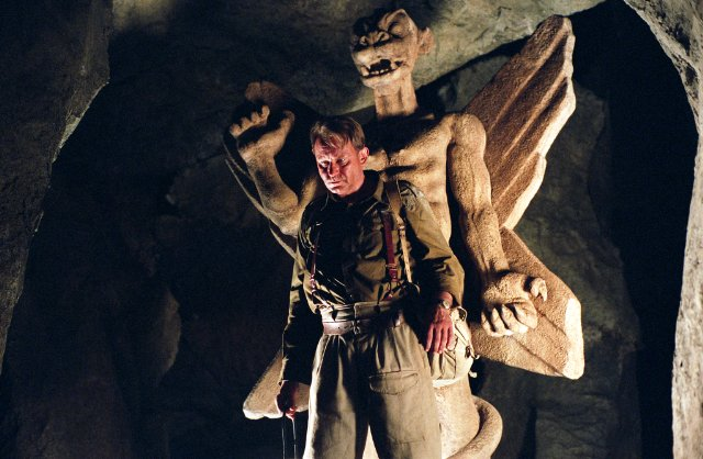 Exorcist: The Beginning [2004] Stellan Skarsgard standing in front of the Pazuzu statue in an underground church scene