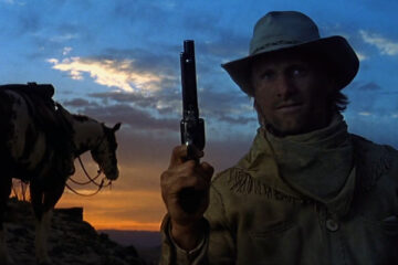 Hidalgo 2004 Movie Viggo Mortensen holding a gun with a horse in the background