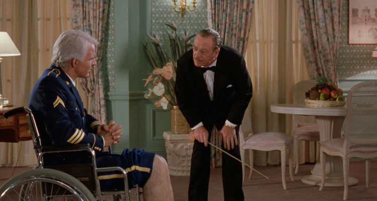 Dirty Rotten Scoundrels 1988 Movie Scene Steve Martin as Freddy Benson sitting in a wheelchair as Michael Caine as Lawrence Jamieson pretending to be Dr. Schaffhausen is a about to whip his legs