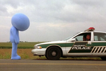 Kabluey 2007 Movie Scene Scott Prendergast as Salman dressed in a giant blue suit standing in front of a police car
