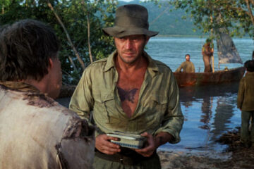 Papillon 1973 Movie Scene Steve McQueen as Henri Papillon Charriere wearing a shirt showing the tattoo on his chest