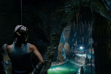 The Cave 2005 Movie Piper Perabo on a rope looking at a cave