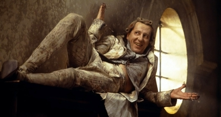 Quills 2000 Movie Geoffrey Rush as Marquis de Sade laying on a cupboard with his arms stretched