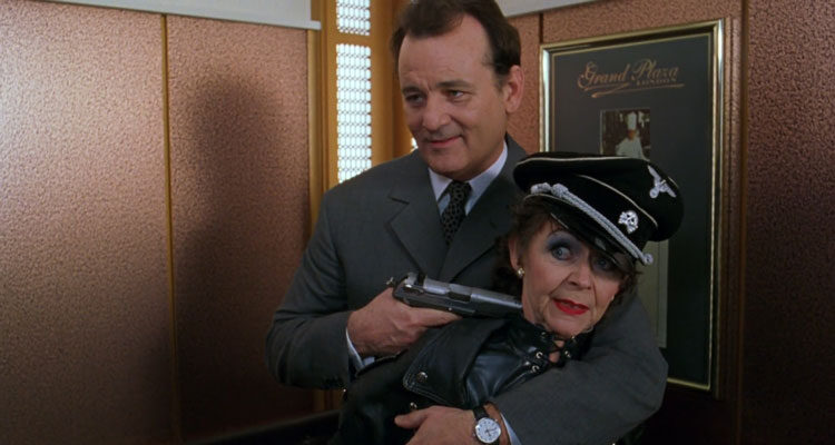 The Man Who Knew Too Little 1997 Movie Bill Murray as Wallace Ritchie holding a gun to an old lady dressed in leather with nazi cap