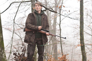 Jagten AKA The Hunt 2012 Movie Mads Mikkelsen as Lucas standing in a forest holding a sniper rifle looking at deer scene