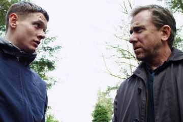 The Liability 2012 Movie Jack O'Connell and Tim Roth looking at each other in the forest scene