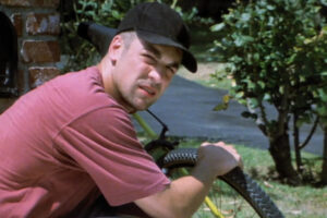 King of the Ants 2003 Movie Chris McKenna as Sean Crawley pretending to be fixing his bike across the accountant's house