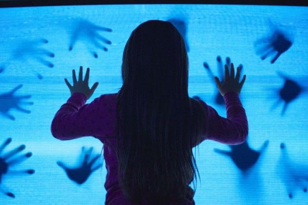 Poltergeist 2015 Movie Scene Kennedi Clements as Madison Bowen holding her hands on the television set