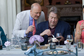 The Hippopotamus 2017 Movie Roger Allam as Ted Wallace and Tim McInnerny as Oliver Mills talking during dinner scene