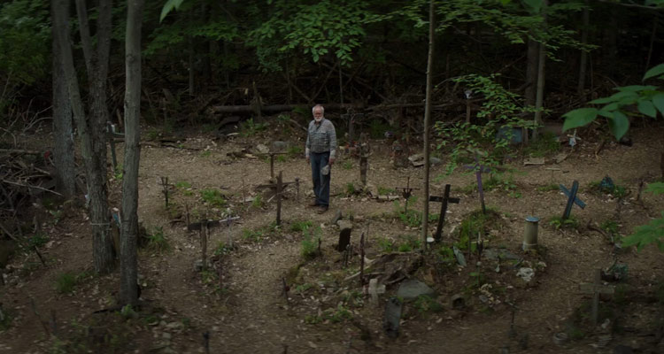 Pet Sematary 2019 Movie Scene John Lithgow as Jud standing in the middle of the cemetery surrounded by graves