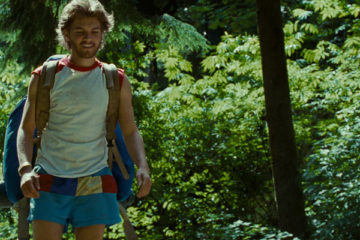 Into The Wild 2007 Movie Image Emile Hirsch as Chris McCandless in a shirt and shorts walking through the forest