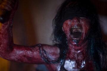 Baskin 2015 Movie Scene Fulya Peker as Mother Butcher all covered in blood, screaming and waving a machete