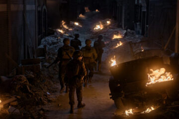 Ghosts of War 2020 Movie Brenton Thwaites, Theo Rossi, Kyle Gallner, Skylar Astin and Alan Ritchson walking through a street filled with rubble and fire on their way to the castle