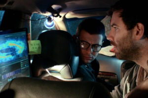 Cosmos 2019 Movie Joshua Ford as Harry Knight and Tom England as Mike Webster looking at the computer rendered image of a universe