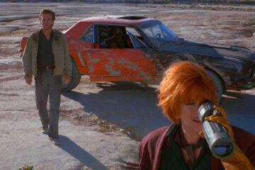 Cherry 2000 1987 Movie David Andrews as Sam Treadwell walking away from the red car and towards Melanie Griffith as E. Johnson looking through the special binoculars