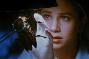 The Mimic 1997 Movie Mira Sorvino holding a giant cockroach