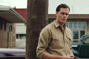 The Devil All the Time 2020 Movie Bill Skarsgård lighting a cigarette in a military uniform