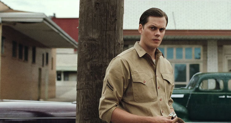 The Devil All the Time 2020 Movie Bill Skarsgård lighting a cigarette in a military uniform