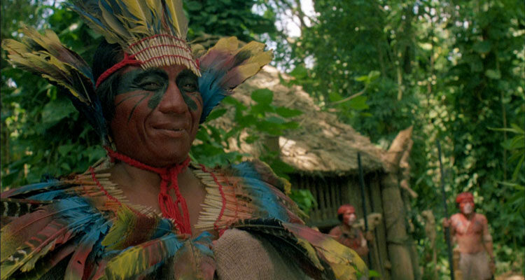 The Serpent and the Rainbow 1988 Movie Amazon shaman wearing bright and colorful feathers smiling as Bill Pullman is hallucinating