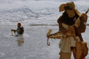 Mindwarp 1992 Movie Bruce Campbell as Stover holding a crossbow dressed in fur while a Crawler is about to throw a sling at him from water