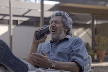 Reality 2014 Movie Alain Chabat sitting in a chair and groaning and screaming into a Dictaphone trying to record the perfect take