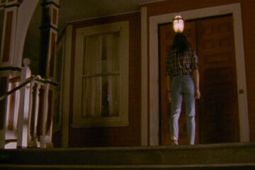 The House of the Devil 2009 Movie Jocelin Donahue in jeans and plaid shirt looking towards the door of the house