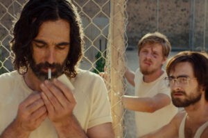 Escape From Pretoria 2020 Movie Daniel Radcliffe and Daniel Webber watching Mark Leonard Winter lighting a cigarette inside the prison