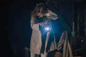 Hereditary 2018 Movie Toni Collette shining a flashlight in her attic