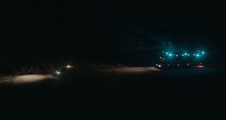 Bajocero 2021 Movie A police car in front of an armored prisoner transport van on a dark road