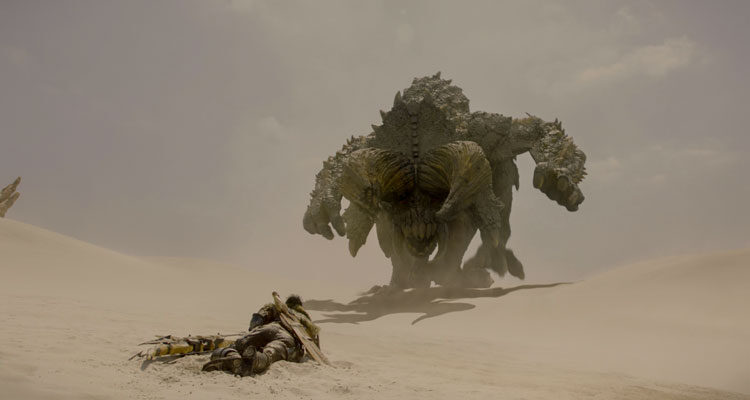 Monster Hunter 2020 Movie Milla Jovovich laying on the ground as a giant monster approaches