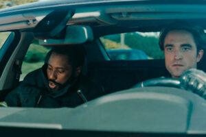 Tenet 2020 Movie John David Washington and Robert Pattinson in a car driving down the highway