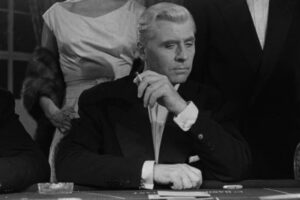 Bob Le Flambeur 1956 Movie Roger Duchesne as Robert 'Bob' Montagné gambling in a casino and smoking a cigarette