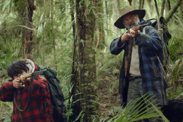 Hunt For The Wilderpeople 2016 Movie Sam Neill and Julian Dennison holding guns in the jungle