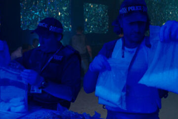 Hyena 2014 Movie Peter Ferdinando as Michael and Gordon Brown as Chris holding bags of mdma and weed after raiding a club