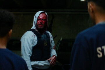 Shorta AKA Enforcement 2020 Movie Jacob Lohmann with a face covered in blood wearing a bulletproof west and a hoodie