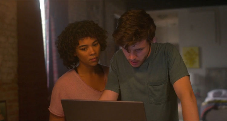 Silk Road 2021 Movie Nick Robinson as Ross Ulbricht and Alexandra Shipp as Julia looking at his laptop