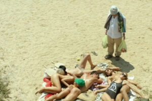 Suntan 2016 Movie Makis Papadimitriou as Kostis holding bags of beer on the beach in front of the gang
