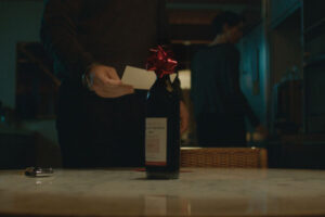 The Gift 2015 Movie Bottle of wine Gordo left as a present on a table with Jason Bateman reading the note