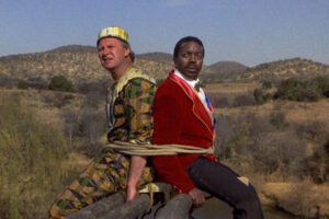 Yankee Zulu 1993 Movie Leon Schuster as Rhino and John Matshikiza as Zulu sitting on a plank with an elephant on the other side