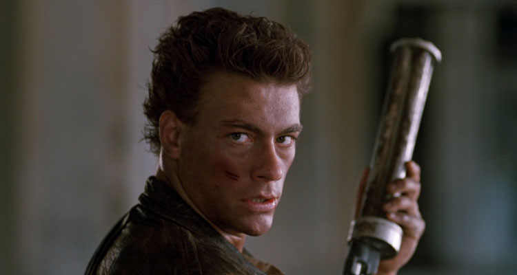 Cyborg 1989 Movie Scene Jean-Claude Van Damme as Gibson Rickenbacker holding a six-shooter and looking at the camera