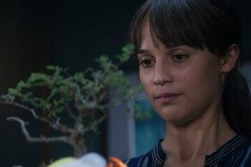 Earthquake Bird 2019 Movie Alicia Vikander as Lucy Fly holding a bonsai tree