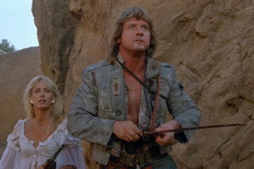 Hell Comes to Frogtown 1988 Movie Scene Sandahl Bergman and Roddy Piper holding a bloody sword fighting frog mutants