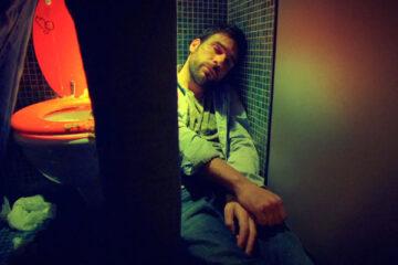 I Can Quit Whenever I Want AKA Smetto Quando Voglio 2014 Movie Scene Edoardo Leo as Pietro Zinni laying passed out in the toilet