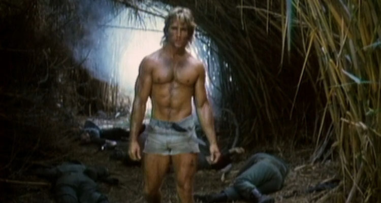 Deadly Prey 1987 Movie Scene Ted Prior as Mike Danton in cutoff jeans shorts showing his muscles as he walks over dead bodies