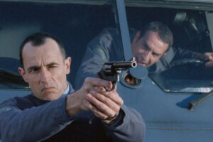 Le Convoyeur AKA Cash Truck 2004 Movie Scene Albert Dupontel as Alexandre Demarre holding a gun in front of the armored car with Jean Dujardin as Jacques