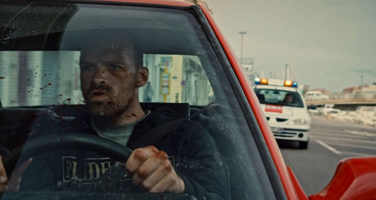 Lost Bullet 2020 Movie Scene Alban Lenoir as Lino driving a red Renault 21 with the police behind him