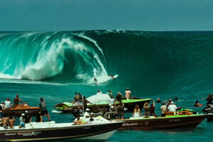 Point Break 2015 Movie Scene Luke Bracey as Utah and Edgar Ramírez as Bodhi riding a giant wave with dozens of onlookers watching from their boats