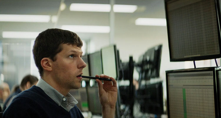 The Hummingbird Project 2018 Movie Scene Jesse Eisenberg as Vincent Zaleski holding a pencil in his mouth and looking at the monitors