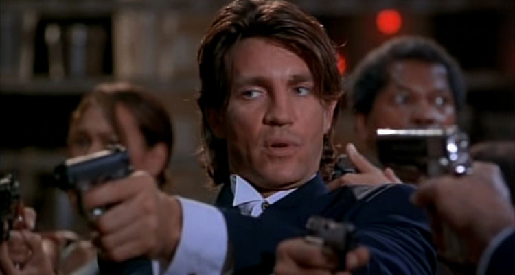 The Immortals 1995 Movie Scene Eric Roberts as Jack holding two guns with Tia Carrere and Clarence Williams III in the background in the kitchen